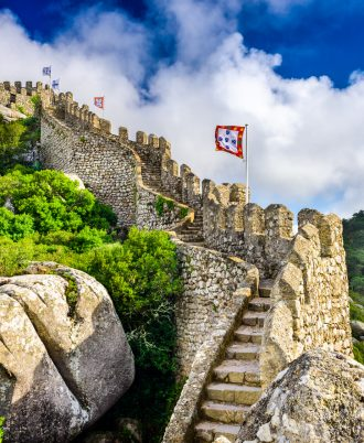 Sintra, Portugal at Castle of the Moors wall with Pena National Palace in the distance.